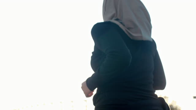 close-up rear view of muslim woman in hijab running in sunset (slow motion) - hijab stock videos & royalty-free footage