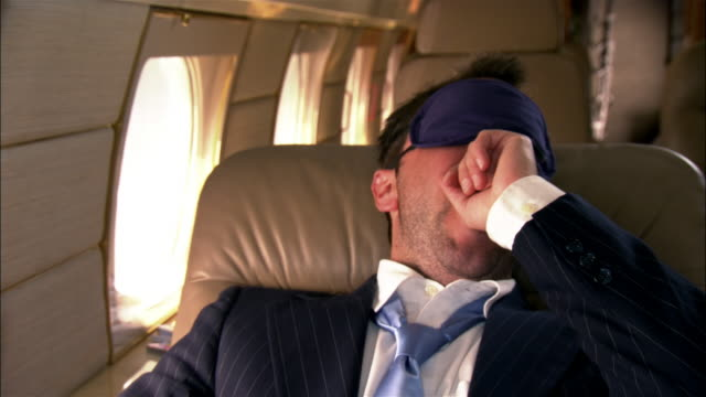 stockvideo's en b-roll-footage met close-up reclining businessman wearing sleep mask and yawning in private airplane - achterover leunen