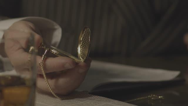 vídeos y material grabado en eventos de stock de close-up reenactment shot of a mob boss examining his gold pocket watch at his desk during prohibition era - crimen organizado