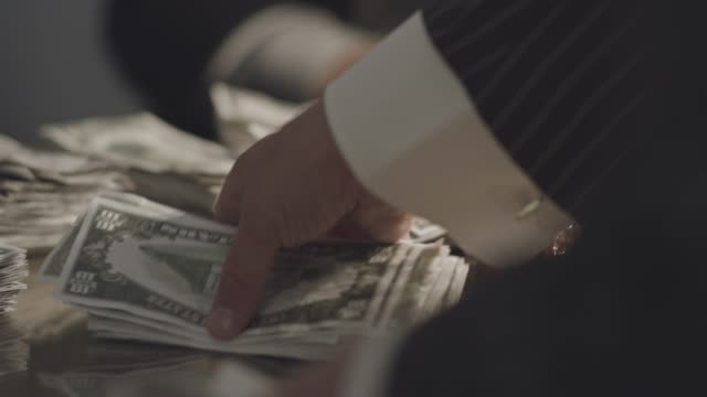 close-up reenactment shot of a mob boss giving an envelope full of cash to a gangster at his desk during prohibition era - organised crime stock videos & royalty-free footage
