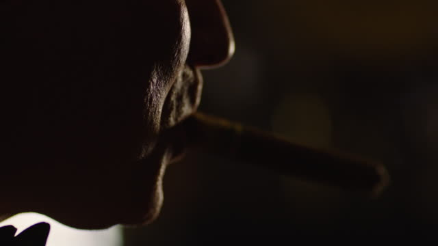 close-up reenactment shot of a profile of a man while smoking cigar in a bar during the 1940s - spion stock-videos und b-roll-filmmaterial