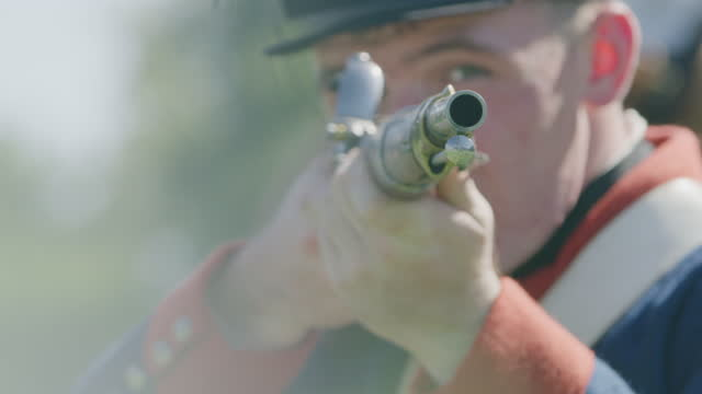 close-up reenactment shot of a soldier aiming with a rifle in the gunpowder smoke during the 18th century - 革命点の映像素材/bロール