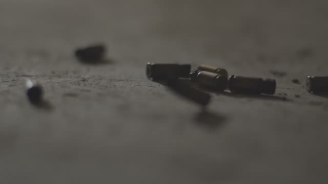 close-up shot of bullet casings falling to concrete floor - organized crime stock videos and b-roll footage