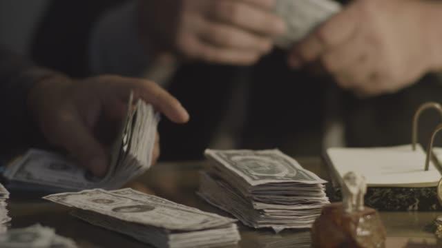 close-up reenactment shot of gangsters stacking up cash on a desk during prohibition era - organized crime stock videos & royalty-free footage