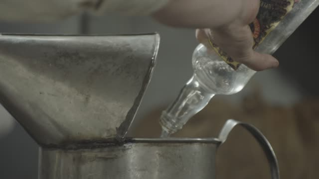 stockvideo's en b-roll-footage met close-up shot of men filling a pouring can with liquor - men