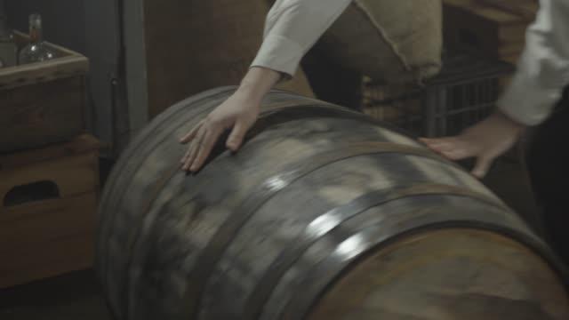 vidéos et rushes de close-up reenactment shot of men rolling barrels during prohibition era - alcool