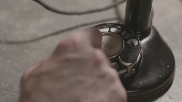 vidéos et rushes de close-up reenactment shot of the hand of a man calling someone on a candlestick telephone during early 1900s - 1920
