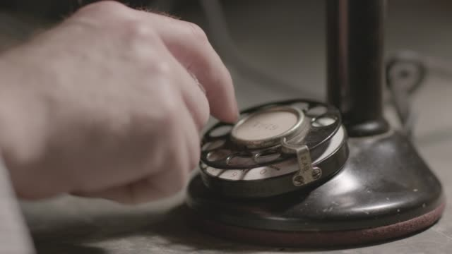 close-up shot of the hand of a man dialing a phone number on a candlestick telephone - disco combinatore video stock e b–roll