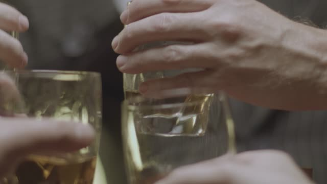 vidéos et rushes de close-up reenactment shot of the hands of a group of men toasting with glasses during prohibition - 1920