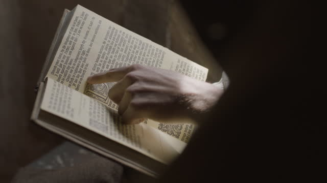 close-up reenactment shot of two people reading a book and pointing at the page during the 17th century - literature stock videos & royalty-free footage
