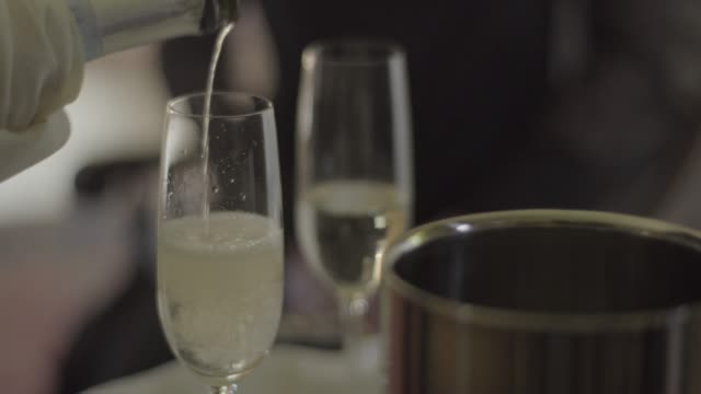 vídeos de stock e filmes b-roll de close-up shot of waiter pouring champagne into glasses and two people taking them - balde de gelo