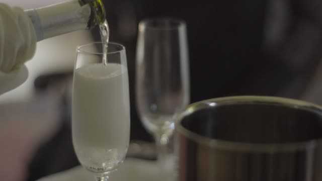 Close-up shot of waiter pouring champagne into glasses