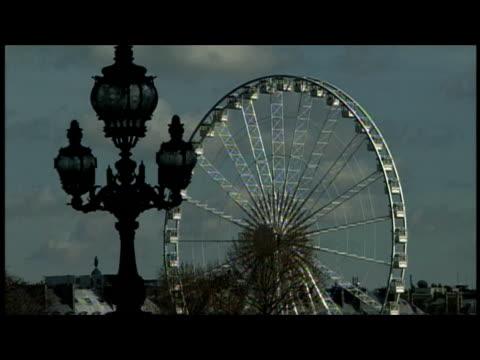 2000 Close-up Roue de Paris, the giant ferris wheel, turning near street light/ Paris, France
