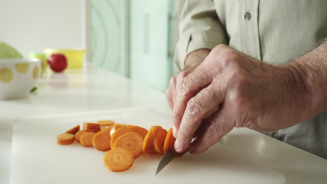 close-up, senior man cooking a healthy meal at home - carrot stock videos and b-roll footage