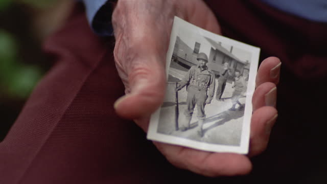 close-up senior man holding old photograph of himself as young soldier wearing military uniform / des moines, king county, washington, usa - veteran stock-videos und b-roll-filmmaterial