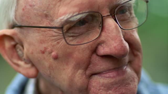 vídeos y material grabado en eventos de stock de close-up senior man wearing eyeglasses and hearing aid / des moines, king county, washington, usa - lunares