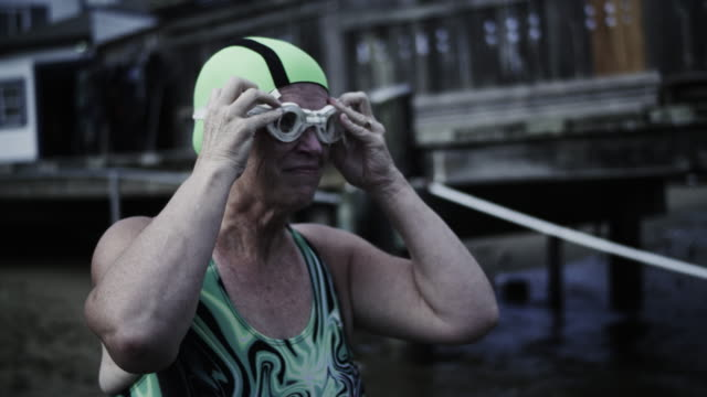 Close-up, senior woman swimmer puts on her goggles in preparation for her swim in San Francisco Bay.