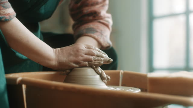 Close-up, senior woman using pottery wheel at atelier