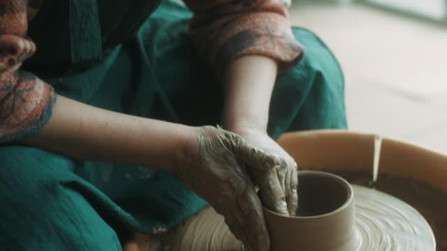 Close-up, senior woman using pottery wheel