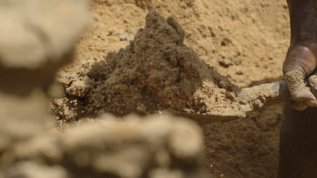 close-up sequence of bare-footed men shovelling sand and mud in a diamond mine pit in sierra leone. - 掘る点の映像素材/bロール