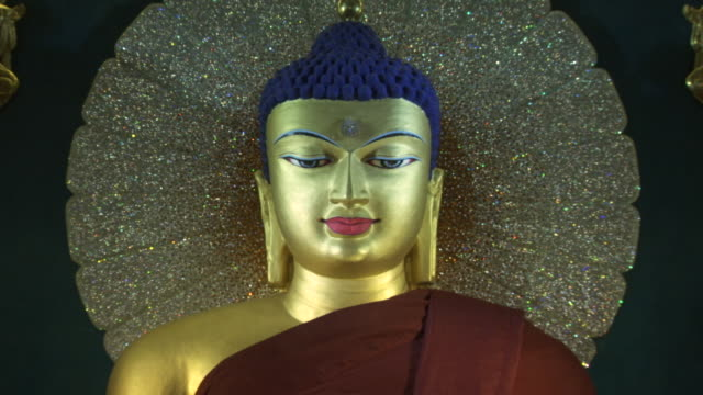 vidéos et rushes de close-up sequence showing a golden depiction of buddha with a twinkling halo at the mahabodhi temple complex in bihar, india. - sculpture production artistique