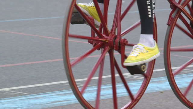 vídeos y material grabado en eventos de stock de close-up sequence showing a man wearing elastane clothing and yellow trainers trying out a red 'boneshaker' bicycle at a velodrome, uk. - bicicleta antigua