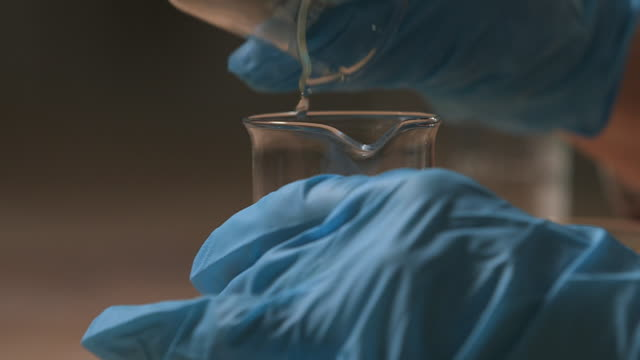 Close-up sequence showing a scientist mixing two clear liquids in a beaker in a demonstration of how nylon is made, UK.