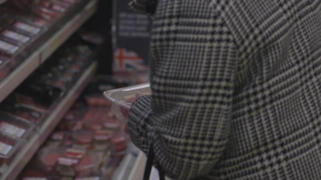 close-up sequence showing a shopper deliberating over beef mince at a tesco supermarket, uk. - tesco点の映像素材/bロール