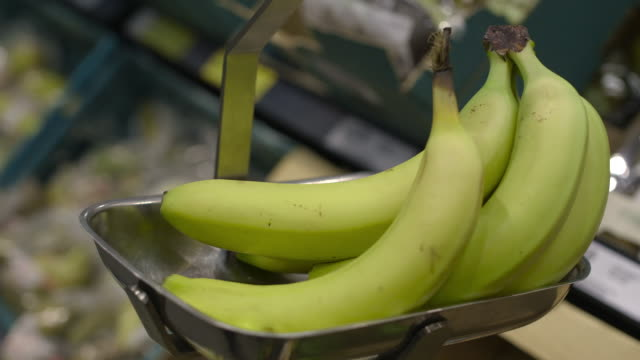 close-up sequence showing a woman using weighing scales to weigh bananas at a uk supermarket. - waage gewichtsmessinstrument stock-videos und b-roll-filmmaterial