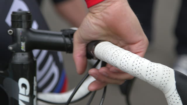 close-up sequence showing cyclists preparing for a race, uk. - fibreglass stock videos and b-roll footage