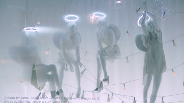closeup sequence showing mannequins dressed as angels seemingly suspended on strings of flashing light bulbs in a selfridges department store window... - espositore per negozio video stock e b–roll