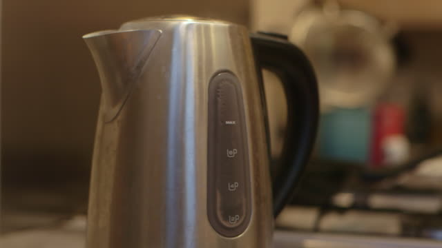 close-up sequence showing steam coming from the spout of a boiling electric kettle in a kitchen, uk. - boiling stock videos & royalty-free footage