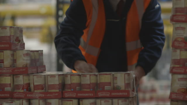 Close-up sequence showing tins of soup being moved by a worker at a large food distribution warehouse in the UK.