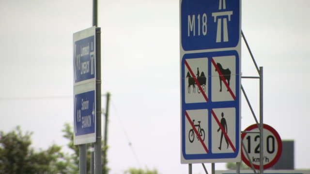 close-up sequence showing traffic and signage at a junction of the m18 motorway in the republic of ireland. - speed limit sign stock videos & royalty-free footage