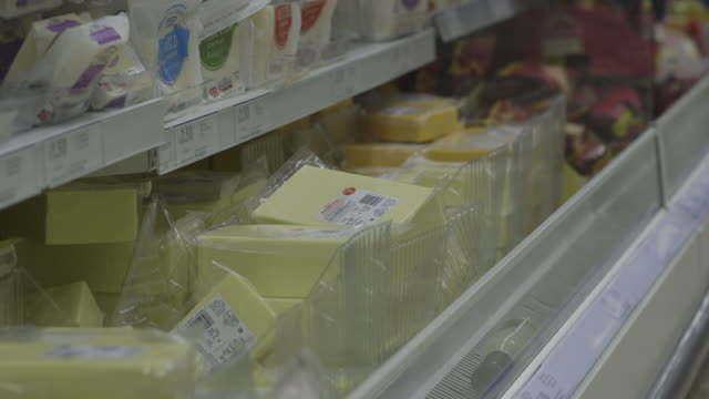 Close-up sequence showing various cheddar cheeses on display on refrigerated shelves at a supermarket in the UK.
