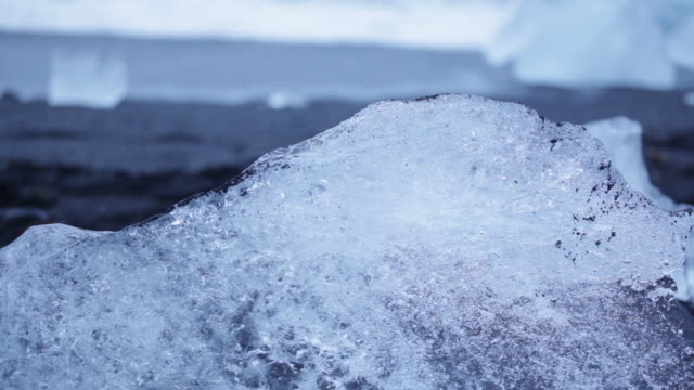vídeos de stock, filmes e b-roll de close-up sequence showing waves splashing over lumps of ice sitting incongruously on a beach in iceland. - neve derretida