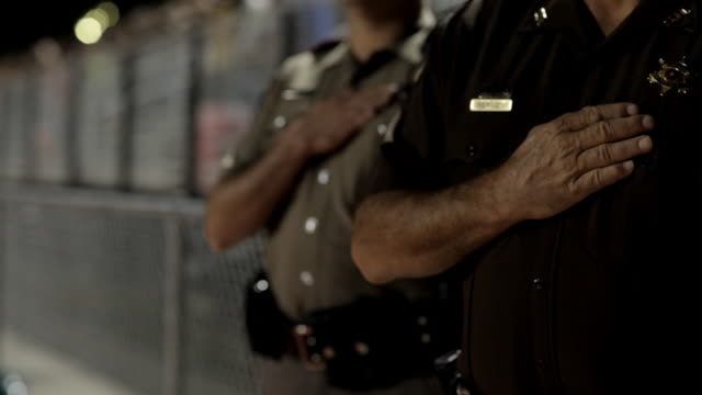 """closeup sheriff and deputy with hands over their hearts during the """"star spangles banner"""" at a friday night high school football game. - hand aufs herz stock-videos und b-roll-filmmaterial"""