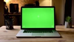 Closeup shoot of the laptop with green screen on the desk in the office indoors capturing the workplace organization