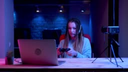 Closeup shoot of young attractive female blogger with dreadlocks in headphones playing video games on the laptop and failing being frustrated with the neon background indoors