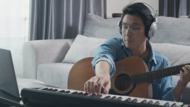 close-up shot asian adult male playing keyboard piano and acoustic guitar in the living room at home. a man playing guitar composing and writing music or recording music to laptop computer. musician writing music by using electric keyboard - musician stock videos & royalty-free footage