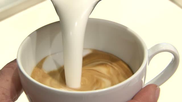vídeos de stock, filmes e b-roll de foto close-up de xícaras de café a ser feitos ao barista - bebida com espuma
