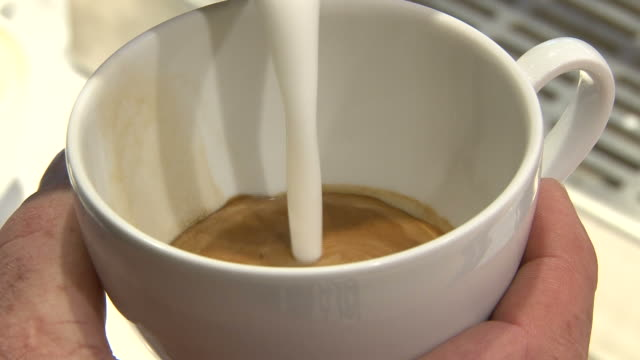 close-up shot coffee cup being made by barista - froth art stock videos and b-roll footage