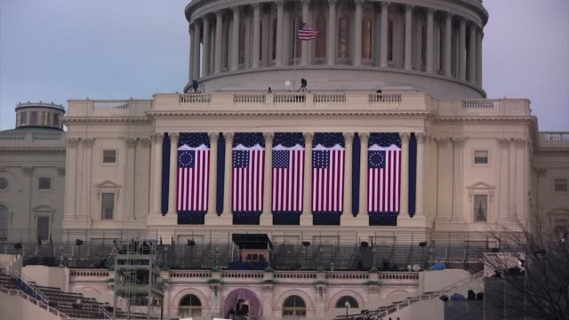 closeup shot five versions of the american flag hang from the front of the united states capitol on the eve of the presidential inauguration of... - inauguration into office stock videos & royalty-free footage