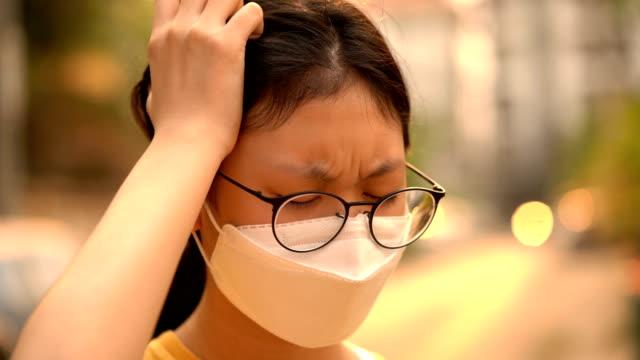 close-up shot girl got headache wearing air pollution mask - air pollution stock videos and b-roll footage