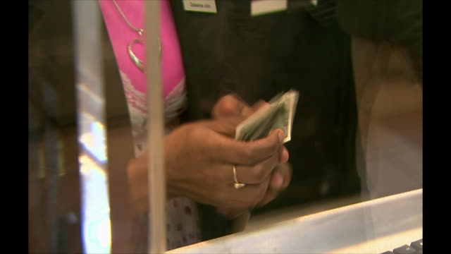 Closeup shot of a bank teller counting out money for a customer