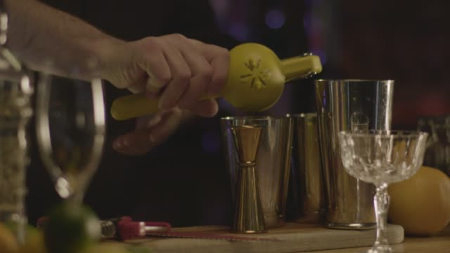 Close-up shot of a bartender making a Scofflaw cocktail