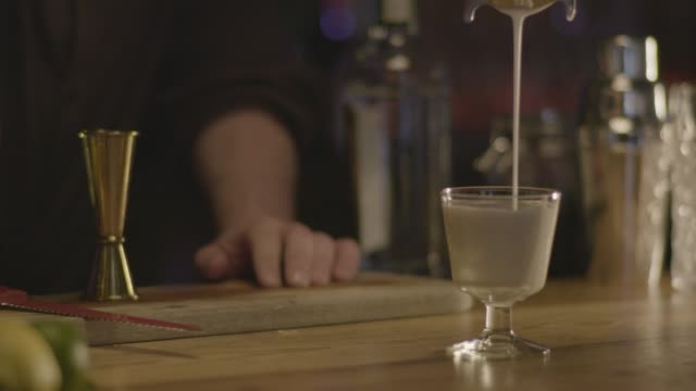 Close-up shot of a bartender making the last steps of Classic Whiskey Sour cocktail