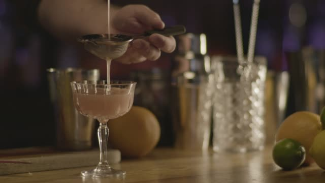 Close-up shot of a bartender making the last steps of the Scofflaw cocktail