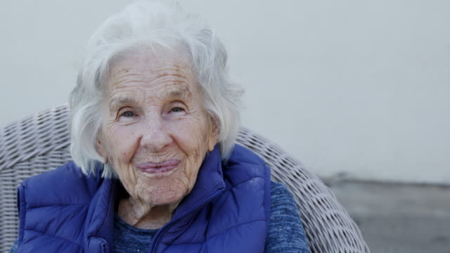 close-up shot of a beautiful 90 plus year-old elderly senior caucasian woman smiling sitting outdoors in the summer - over 80 stock videos & royalty-free footage