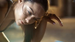 Close-up Shot of a Beautiful Athletic Woman Wipes Sweat from Her Forehead with a Hand, Looks into Camera. She's Tired after Intensive Cross Fitness Exercise.